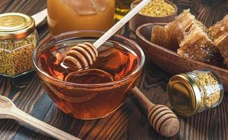 Honey in glass jar with honey dipper over wooden background photo