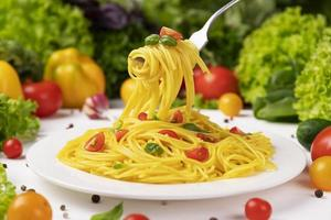 Plate of italian pasta spaghetti on fork with tomatoes and basil photo
