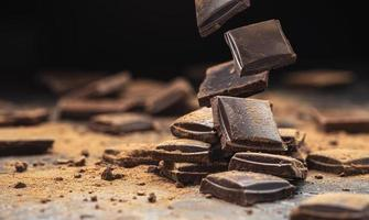 Falling broken chocolate bars on black background photo