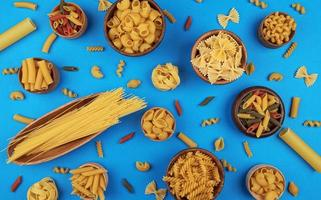 Different pasta types on blue background top view photo