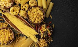 Different pasta types on black background with copy space for text photo