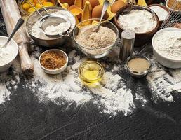 Baking ingredients on black background with copy space photo