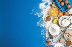 Baking ingredients on blue color background top view photo