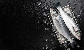 Seabass fish on metal tray on black stone background photo