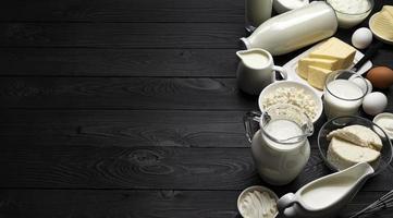 Productos lácteos en la vista superior de fondo de madera negra foto