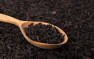 Dry tea leaves in wooden spoon isolated on dark background photo
