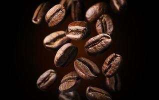 Roasted falling or flying coffee beans on black background close up photo