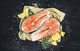 Salmon steaks on black background top view photo filtered in vintage style