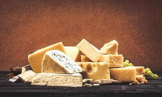 Different types of cheese on black wooden table background photo