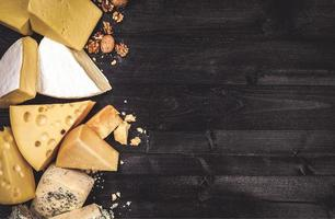 Various types of cheese on black wooden background with copy space photo