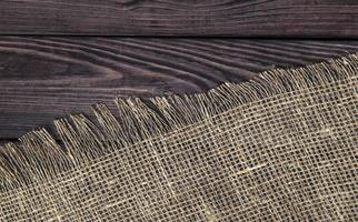 Madera oscura con vista superior de textura de arpillera vieja foto