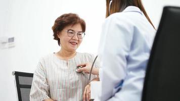 Joven médico con estetoscopio para examinar el corazón del paciente video