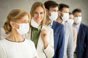 Professionals in a row with woman taking off her facial mask photo