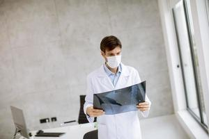 Doctor in an office looking at an x-ray photo
