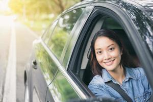 Beautiful Asian woman smiling and driving a car photo