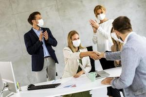 Business agreement with masks on photo