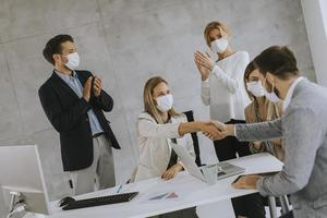 Business agreement with people wearing masks photo
