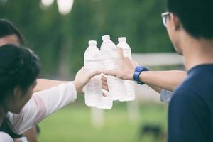Students holding cold water bottles on campus photo