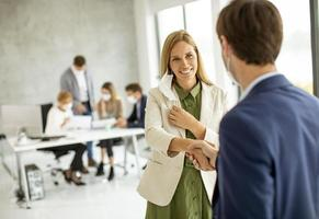 Woman taking off mask in a meeting photo