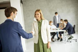Woman taking off her mask in a meeting photo