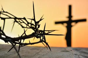 Crown of thorns of Jesus Christ against silhouette of Catholic cross at sunset background photo