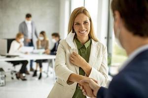 Woman shaking hands and taking mask off photo