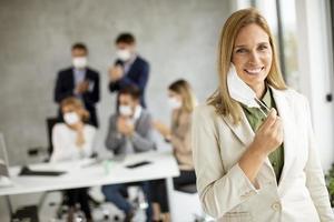 Businesswoman taking mask off photo