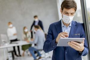 Man wearing a mask using a tablet photo