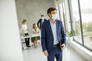 Man standing in front of team with a mask on photo