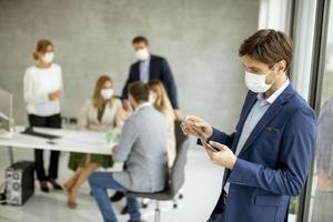 Man using a tablet while wearing a mask photo