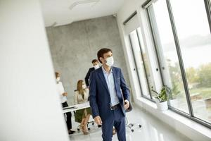 Man walking in an office with a mask on photo