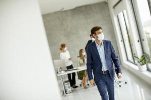 Man wearing a mask and walking away from a meeting photo
