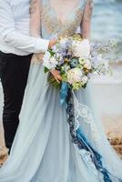 Bride in a blue dress with groom walking along the ocean shore photo