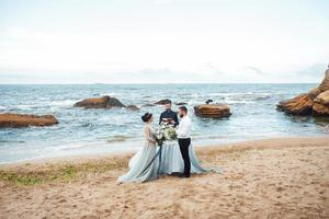 Wedding couple on the ocean with a priest photo