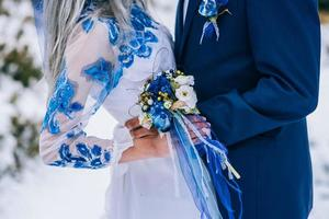 Groom in a blue suit and bride in white in the mountains Carpathians photo