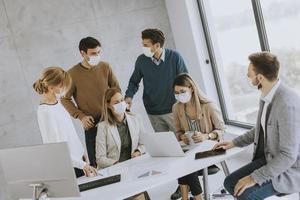 Masked people in a meeting in a modern office photo