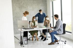 Profesionales enmascarados en una reunión en una oficina moderna foto