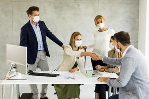 Business agreement with professions wearing masks photo