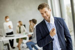 Smiling businessman taking off mask photo