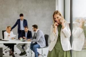 Professional on phone with meeting going on photo