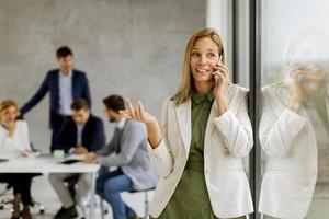 Businesswoman on phone with team in the background photo