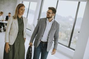 Business couple walking together in office space photo