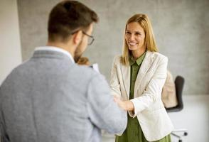Two business people shaking hands in an office photo