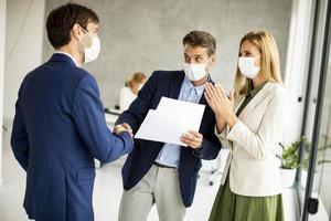 Three masked professionals meeting photo