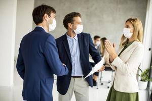 Three masked professionals talking photo