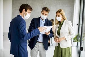 Three masked business people with document photo