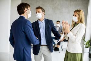 tres empresarios enmascarados haciendo un acuerdo foto