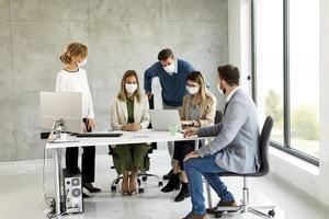 Personas enmascaradas en una reunión mirando un portátil. foto