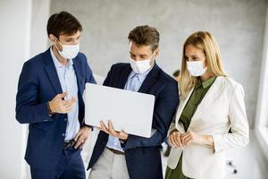 Tres profesionales enmascarados mirando un portátil. foto