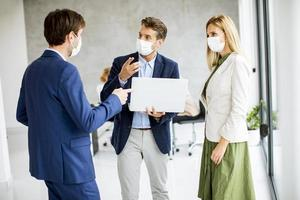 Three masked professionals standing and talking photo
